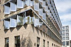 In der Gasse Weinhofberg ergänzen die Architekten die Fassadenstruktur im Erdgeschoss um ein weiteres Element: mit einer Reihe kleinformatiger Rundfenster, die gekippt werden können