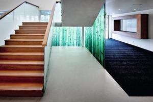 """<div class=""""16.6 Bildunterschrift"""">Die puristischen Waldanspielungen setzen sich im Gebäudeinneren fort. Hier sorgen Verkleidungen, Garderoben und  Treppen aus Holz, Stein und Glas für Naturassoziationen</div>"""