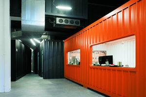 In dem orangefarbenen Container befinden sich die Arbeitsplätze der Geschäftsleitung, die sich ebenso wie die anderen Mitarbeiter eine Arbeitsbank teilen.In einem der schwarzen Container ist die Verwaltung untergebracht, in dem anderen die sanitären Anlagen