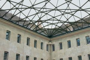 Die Tragstruktur des Glasdaches besteht aus einem engmaschigen Netz aus vollen Stahlprofilen und besitzt eine maximale Höhe von nur 5m bei einer diagonalen Überspannung von 47,94m
