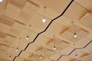 Unter der Decke hängen regelmäßig gefaltete Gipskartonelemente mit weiteren gitterförmigen Schallreflektoren, die speziell dazu beitragen, dass die Musiker und Musikerinnen sich und ihre Instrumente besser hören