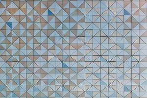 Die vorgehängte Fassade besteht aus vorgefertigten Elementen mit umlaufendem Aluprofil und jeweils acht Dreiecken aus Sonnenschutzglas. Die Wirkung ist die eines Paillettenkleides, welches das skulpturale und schlankeVolumen betont