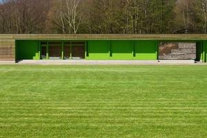 Leuchtendes Grün hinter Holzlamellen für Clubraum und Umkleiden – das Sportlergebäude in Hemer <br />