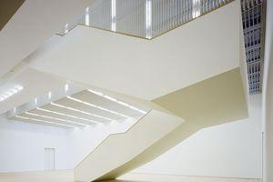 """Ausgestellte Lichtlenkscheiben reflektieren Tageslicht in das Treppenhaus und die Ausstellungsräume<br /><br /><div class=""""10.6 Bildunterschrift"""">Der tageslichthelle Patio erweitert den schlanken Museumsbau unterirdisch. Das Licht wird über Bodenroste und Lamellen gefiltert</div>"""