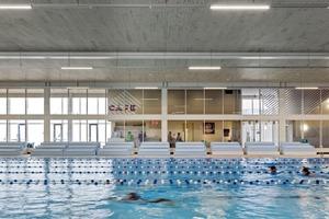 Durch die komplett verglaste Trennwand zwischen der Bar und der Schwimmhalle gelangt − zusätzlich zur Glasfassade im Westen – viel indirektes Licht ins Schwimmbad