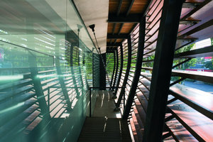 Gebogene Doppel-T-Träger sind durch Stahlstäbe von der Stahlbeton-Glas-Fassade des Betonkubus abgehängt und bilden die vertikale Tragstruktur der Holzfassade. An den Trägern angeschweißte Stahl-profile nehmen die wellenförmig zugeschnittenen Zedernholzplanken auf
