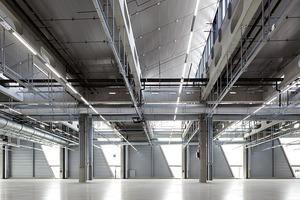 Die ovalen Aussparungen lassen das einfallende Licht der Sheddächer in den Hallenraum und nehmen zusätzlich die Leitungsführung auf