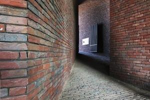"""<div class=""""10.6 Bildunterschrift"""">Um der Kaninchenröhre einen eigenständigen Charakter zu geben, entschlossen sich die Architekten, nicht nur die Wände, sondern auch den Boden und das Dach mit geklebten Klinkerziegeln zu gestalten. Das Baumaterial schafft die Verbindung zwischen Bestandsbauten und Zubau, der den neu gestalteten Innenhof vor den westlichen Winden schützt </div>"""