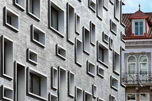 Die Fassadengestaltung mit ihren prägnanten Öffnungen generiert sich aus dem Fassadenmuster des umliegenden Bestands