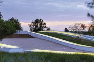 das begrünte dach ist über eine sanft ansteigende Rampe (9m Höhenunterschied) begehbar. Der Landschaftsarchitekt Regis Guignard erzeugte durch seine Planung den Eindruck, inmitten sanfter Hügel zu stehen<br />