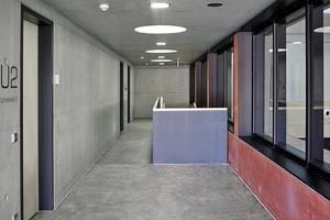 Im Inneren des Gebäudes prägen Sichtbeton, Estrich und Holz den reduzierten Raumeindruck. Die rote Sichtbetonwand setzt sich im Inneren fort