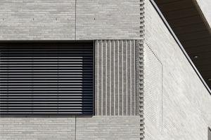 """Um einen Klinker zu erhalten, der den Ansprüchen der Architekten entspricht, wurden von Röben mehrere Oberflächen entwickelt, die in Farbigkeit, Haptik und Textur variierten. Zum Einsatz kam schließlich ein Klinker mit einer rauen Oberfläche, (Yukon). Er wurde nicht nur ein einem """"wilden Verband"""" verbaut; die Fassade erhielt ein lebhafteres Bild durch das einfügen von Klinkern die auf 2/3 ihrer Länge gekürzt wurden<br />"""
