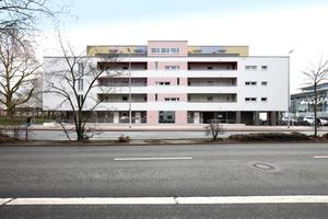 Die Einschnitte in die Putzfassade sind die Laubengänge zu den mit öffentlichem Geld geförderten Wohnungen