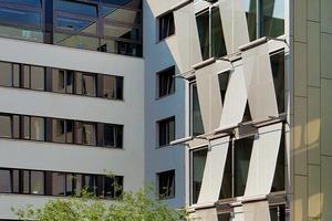 Ein Relief aus außenliegendem Sonnenschutz strukturiert die Fassade zum Innenhof. Das textile Material trägt zum Mikroklima im und am Gebäude bei