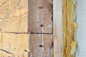 Von außen nur noch von Holzschindeln geschützt, erfüllte dieser ursprüngliche Wandaufbau lange seine Aufgabe des Wetterschutzes. Für die heutigen Anforderungen an die Energieeffizienz ist dies nicht weiter tragbar. Um die vorgefertigten Holzrahmen bündig ansetzen zu können, wurden die Ungenauigkeiten des Bestandes mittels einer gedämmten Ausgleichsebene installiert