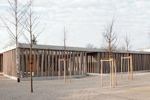 Der das Dach tragende Holzstützenwald reflektiert den umliegenden Bewuchs<br />