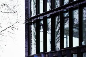 """Das Gebäude wirkt durch sein Objekthaftigkeit und Transparenz wie ein """"Stahlbau"""". Der Neubau vermittelt zwischen den Bestandsgebäuden W5 und W9 mit ihren (Stahlgerüst-) Dachaufbauten und führt deren Erscheinung mit einer schwarz polyspektralen Beschichtung ganz selbstverständlich fort. Unterzüge als Fertigbauteile (vorgespannter Stahl, (b x h, 20 x 60 cm) ermöglichen eine Spannweite von 16m und geben dem Gebäude die transparente Erscheinung. Die Fassade besteht aus rund 250 unterschiedlich gewinkelten schwarz-polyspektral beschichteten Edelstahlblechen"""