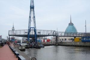 Für den Einhub des drehbaren Mittelteils wurde ein spezieller Schwimmkran aus den Niederlanden überführt. Nach der Aufstellung des stählernen Drehpfeilers im Hafenbecken konnte der Stahlüberbau millimetergenau auf den vorbereiteten Drehkranz abgesetzt und verschraubt werden<br />