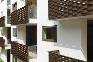 Es gibt präzise Einschnitte in die Fassade, die den Einblick verwehren, aber Ausblicke erlauben. Die geflochtenen, bronzefarbene Balkon-Edelstahl-Brüstungen sind durch einen extrem weit abstehenden und Handlauf kindersicher<br />
