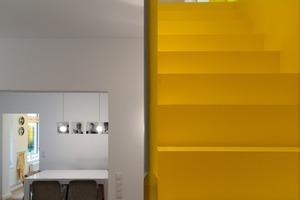 Die Trittstufen sind weiß lackiert und führen auf dem Weg nach unten zum weißen Wohnzimmermöbel. Die gel-ben Setzstufen bilden auf dem Weg nach oben eine Einheit mit dem monochromen Treppenraum<br />