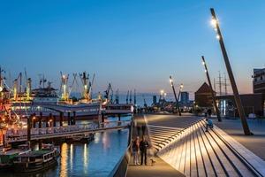 """In Anlehnung an die Schiffsmasten und Kräne im Hamburger Hafen wurden die Lichtmasten an der Promenade nicht senkrecht, sondern mit einer Neigung von 15° montiert. Um eine """"Stadienwirkung"""" bei gleichmäßiger Beleuchtung zu vermeiden, planten Architekten und Lichtdesigner die Beleuchtung so, dass hellere und dunklere Lichtbereiche entstehen"""