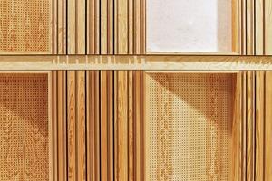 Wechsel von Kassettenelementen, gelocht aus Holz, längs gefräst (MDF + Furnier) und mit weißem Filz belegt