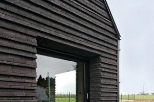 Durch die in die Laibung zurückversetzten, innenliegenden Fens-tern schufen die Architekten den Eindruck von großen Löchern in einem massiven Steinblock