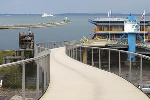 Die Fußgängerbrücke schlängelt sich über 243m hinunter in den Hafen. Die Krümmung generiert Länge, so konnte die Steigung &lt;6,5% gehalten werden<br />