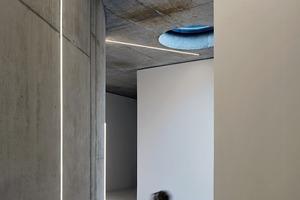 Der Hauseingang schneidet sich tief und ver-winkelt in das Volumen ein. Er verengt und weitet sich, inszeniert Dunkel und Hell von rohem Beton und abstrakten LED-Lichtstreifen