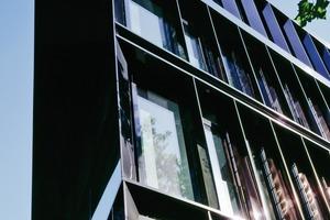 Die Fassaden der Nord-, Süd- und Westseite werden mit einer umlaufenden Konstruktion von Vertikallamellen aus schwarzem Edelstahl vor einer Pfosten-Riegelkonstruktion bekleidet
