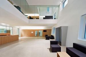 Das Foyer erlaubt vielfältige Sichtbeziehungen. Die reduzierte Materialität mit verputzten Wänden, dem versiegelten Zementestrich als Boden und Glas lassen den Raum wohltuend offen