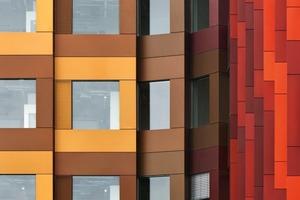 Jedes Fassadenelement gruppiert vier gleichfarbige Alupaneele um ein rahmenloses Fenster<br />