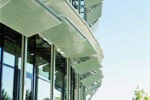 Edelstahl-Schwerter wurden an die polygonale Glasfassade befestigt und auf diese Edelstahlführungsschienen. In diesen Schienen befinden sich die Rollapparate und Elektro-Getriebemotoren. Durch Laufwagen und ausgeklügeltenLagerungen können 112 Elemente individuell bewegt werden