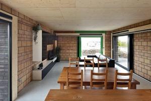 Der offene, 48m² große Wohn-Essbereich wird durch eine Ziegelwand, hinter der die Treppe liegt, vom Eingangsbereich getrennt. Hinter den Verblendungen der Fenster- und Türrahmen verlaufen Elektroleitungen aus den oberen Geschossen